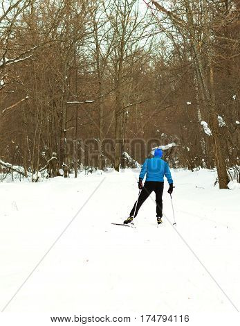 Skiing in the morning in the beautiful winter forest. Ice ridge course skiing. Healthy lifestyle concept.
