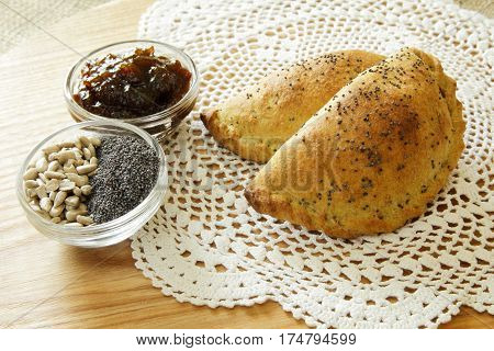 Russian pirozhki, baked patties or pies on basket with jam, sunflower seeds and poppy