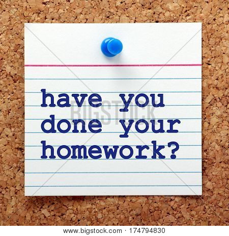 The words Have You Done Your Homework in blue text on a note card pinned to a cork notice board as a reminder that preparation is necessary in business and education
