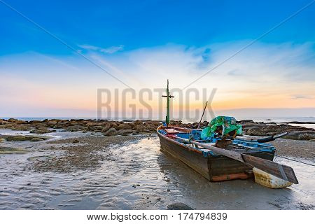 small wooden fishing boat dock on the beach with the rock in seascape sunset sky