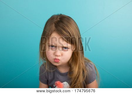 Little girl with sassy expression against teal background