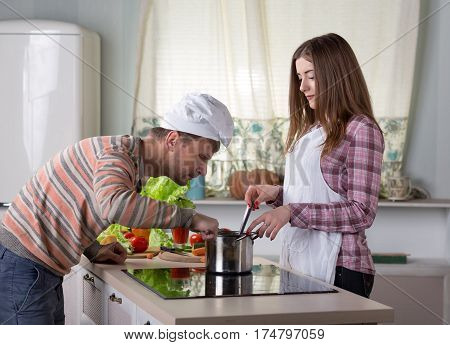 Wife and Husband cooking Dinner together at Home Kitchen Interior Woman in white Apron and Man with Cook Cap stirs and tastes Soup in steel Pan.