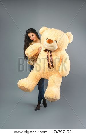 Young beautiful girl with big teddy bear soft toy happy smiling and playing on grey background.