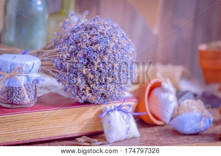 A bunch of bright blue colored dry lavender in a composition on a table in daylight. Vintage still life