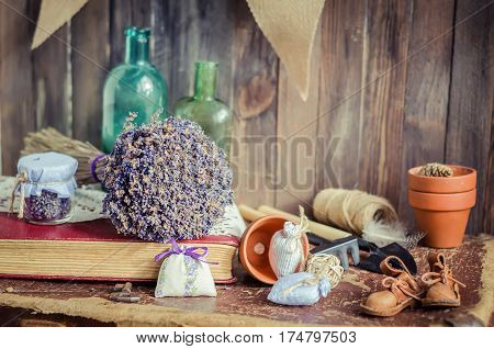 The bunch of dry lavender with different objects on a table in daylight. Horizontal studio shot. Vintage still life