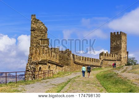 Background landscape view tourists walk in a Sudak fortress amidst the ruins of ancient towers in the Crimea  in the spring