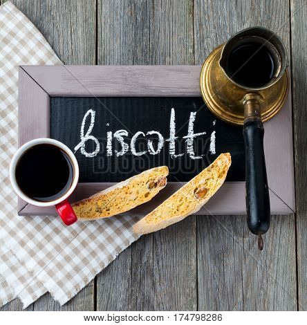 Homemade biscotti with nuts and a cup of coffee on the old wooden table background. Selective focus.Top view.