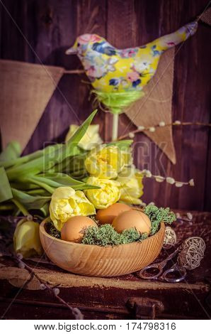 The Easter composition with tulips, eggs in a wooden bowl and textile bird in daylight. Spring morning still life