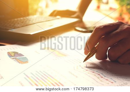 Man Holding Pen And Thinking Calculate Cost And Expenses And Using Laptop For Search Data Result.