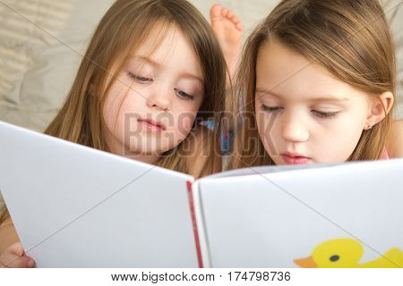 Little girls reading a story book together