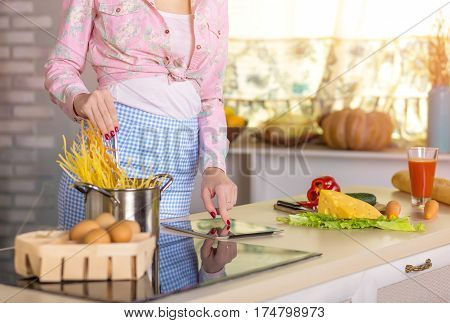 Hands and Body of Woman in home casual Clothing and domestic Kitchen Interior cooking Pasta and reading Recipe on Tablet Computer