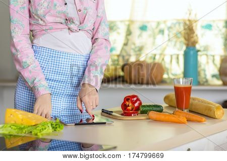 Woman cooking Dish with Cheese Salad Carrot Cucumber ad red Pepper following Recipe on screen of Tablet PC in domestic Kitchen Interior and warm Sunlight throw Window.