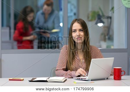 Female Entrepreneur sitting at Office Table with portable Computer and looking into Camera