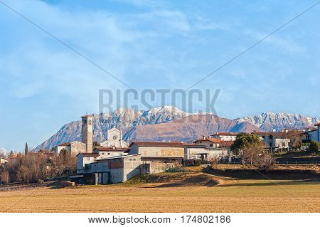 Rural landscape with hamlet fields and mountains in the background.