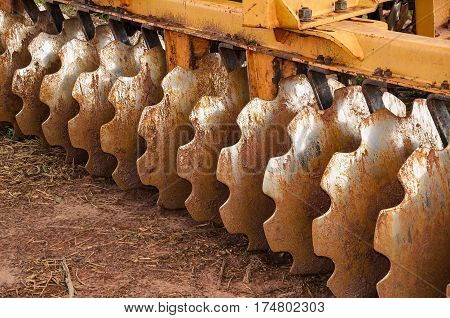 Close the blades of a tractor that plows the land. Tractor blades dirty with dirt.