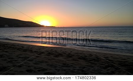 Sunset with a calm sea, sand, and a hill near the horizon.