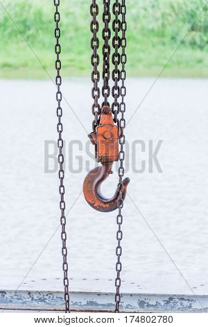 old orange hook and chain near river