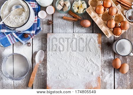 Baking background. Cooking ingredients for dough and pastry making and sprinkled with flour board on rustic wood. Top view with copy space, mockup for menu, recipe or culinary classes.