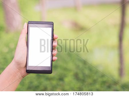 Hands of young woman holding mobile smartphone while walking the park.