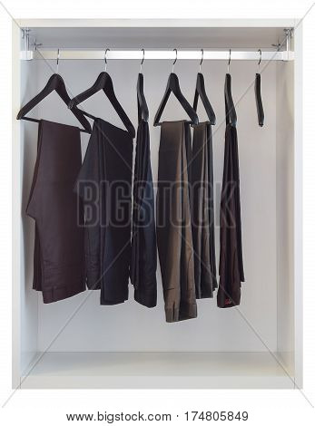 Modern Closet With Row Of Pants Hanging In White Wardrobe - Isolated On White Background