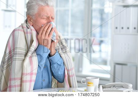 Portrait of a sick elderly man with pills