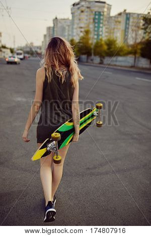 Beautiful young tattooed woman with his longboard on the road in the city in sunny weather. Back view