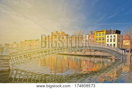 beautiful irish landmark in dublin city. famous ha-penny bridge set in a dublin cityscape skyline on the liffey river.