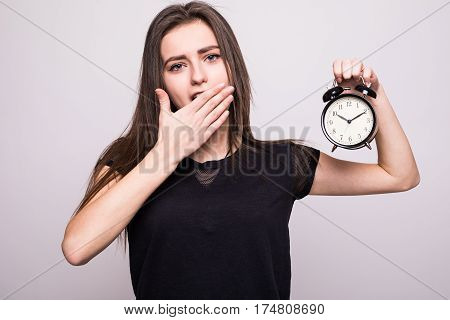 young smiling woman with alarm clock isolated white grey wall background. Human face expression. Time, punctuality, busy schedule concept