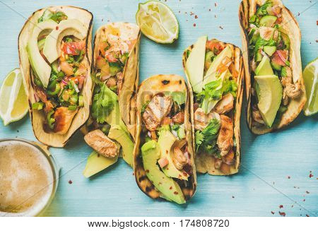 Healthy corn tortillas with grilled chicken, avocado, fresh salsa, limes and beer in glass over blue wooden background, top view. Gluten-free, allergy-friendly, weight loss, dieting concept