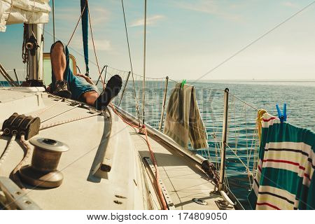 Water traveling adventure concept. Man relaxing lying on sporty yacht front blue calm water sunny weather sky with white clouds.