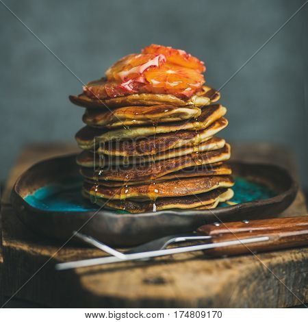 Homemade pancakes with honey, bloody orange slices and mint leaves for breakfast on blue ceramic plate over rustic wooden board, grey plywood wall at background, selective focus, square crop