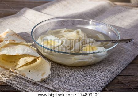 cup of chicken soup with noodles and eggs and pita bread