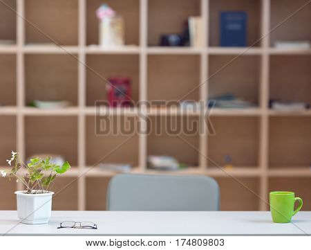 Cozy working Place on Wood Wall background - grey Table with Flower green Coffee Mug and Glasses and wooden Cupboard with Shelves on blurred Background
