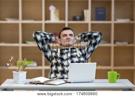 Relaxed young Man in casual Shirt sitting at grey working Place with Computer Flower Papers and Tea Mug smiling Face thinking pensive Face on wooden Wall Background - focus on Computer.