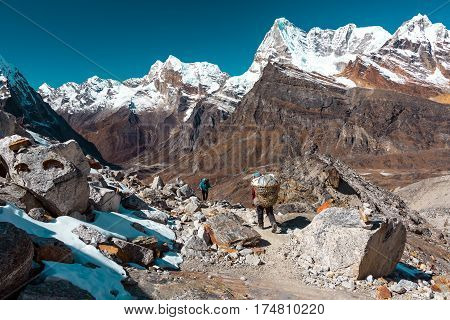 High Mountains Panorama and rocky Footpath between peaces of Snow Nepalese Porter carrying items in traditional Basket and European Hiker walking