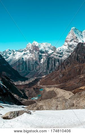 Snowy Glacier and Mountains Panorama Valley and Lakes in Himalaya pointed Peaks and bright Sky daylight View vertical composition