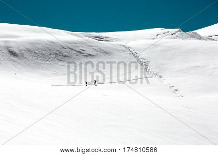 High Altitude Mountain Slope Glacier covered by heavy Winter Snow Two Climbers walking on and leaving deep Trail behind