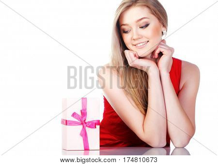 Beautiful young girl in a red dress with a gift.