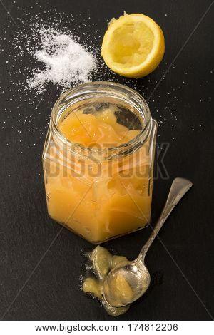 fresh home made lemon curd in a glass caster sugar and half lemon on slate