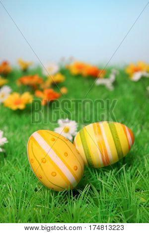 Frühjahrsdekoration mit Ostereiern und Blumen auf einer grünen Wiese
