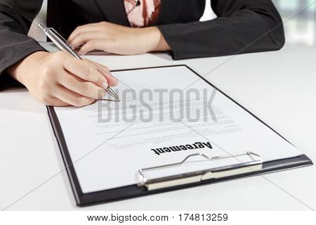 Hands of business woman signing the agreement document with pen on desk - business concept