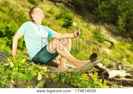 Outdoor nature relaxation concept. Handsome man spending his free time outside during summertime