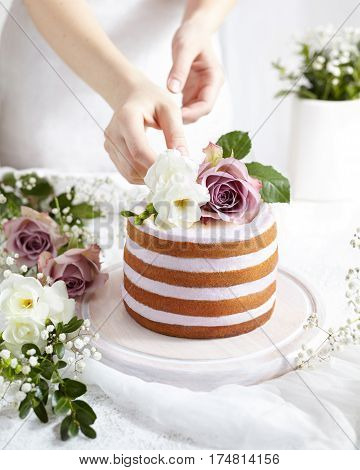 Spring mood. Sponge cake with whipped cream decorated flowers roses and freesia. Tender wedding cake in white with pastel colors. Delikate female hands in the frame A big cake.