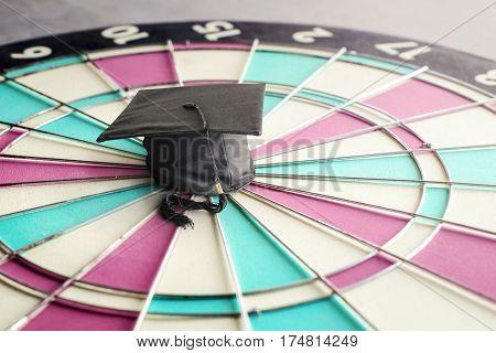 congratulations graduates cap on dartboard education target concept.