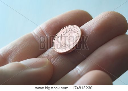A male thumb and index finger gripping a one Euro cent Coin.