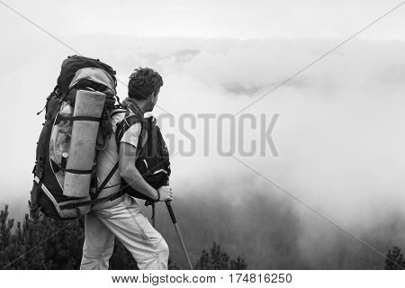 Traveler man with a backpack standing in the mountains above the clouds and looks into the distance - not an easy expedition. Black and white image.