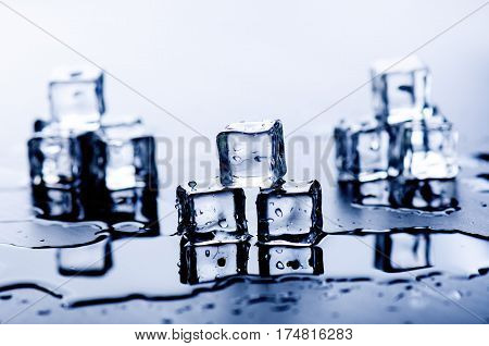 Iced cubes melting on a blue table with reflection. Water. Melting of ice.