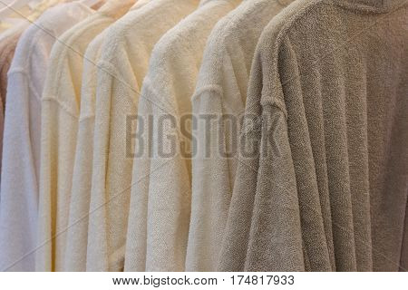 White and beige robes hanging in the closet
