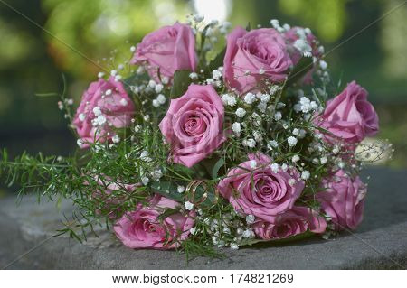 pink rose wedding bouquet with two gold ring