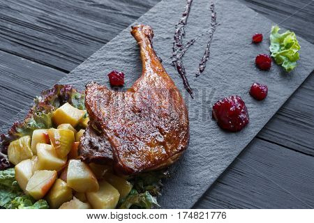 Roasted duck leg closeup served with apples and cherry sauce. Restaurant food on black slate plate at wood table
